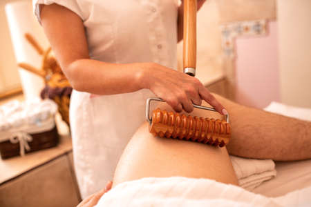 Thigh massage with a handle extension wooden roller, positive life concept