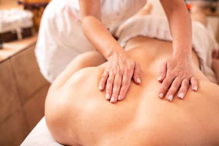 Masseuse with her strong and muscular client in wellness studio