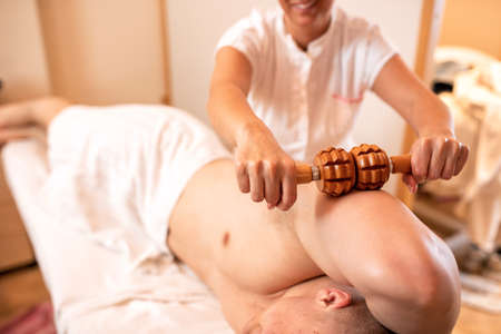 Triceps massage with a wooden roller tool, muscle forming massage