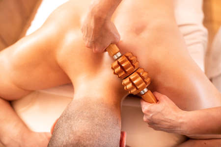 Muscle forming massage with a wooden roller, relaxing time concept