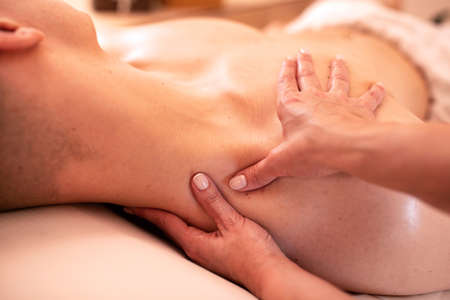 Masseuse applying pressure to the neck area of a young man