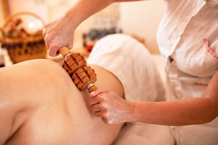 Young strong man having a back massage with a wooden roller Фото со стока