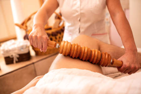 Madero therapy with wooden tools applied on thigh area Фото со стока