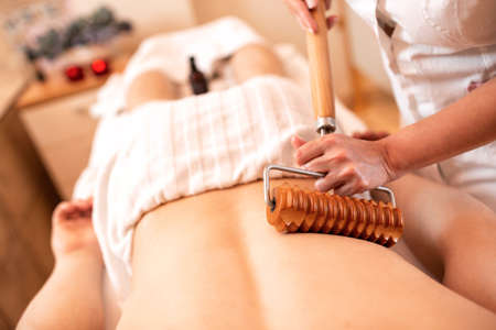 Back area massage with wooden massager, back massage concept Фото со стока