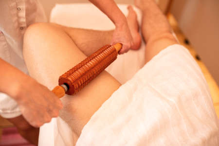 Wooden roller tool used for thigh massage, leg massage concept