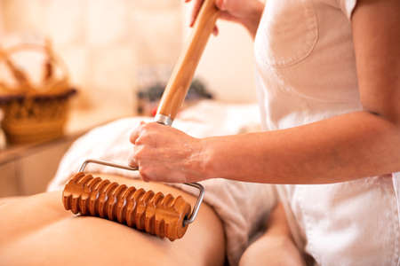 Back massage with a wooden roller that has an extended handle for providing the ability of inducing greater pressure