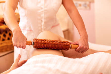 Massage treatment with a wooden roller for acceleration of blood circulation, healthy life concept