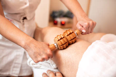 Small wooden roller applied for thigh massage, stimulation of the lymphatic system Фото со стока