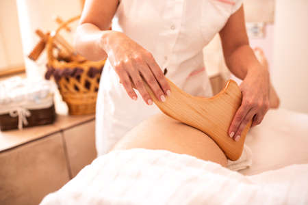 Thigh massage in close up with a wooden tool, relax massage