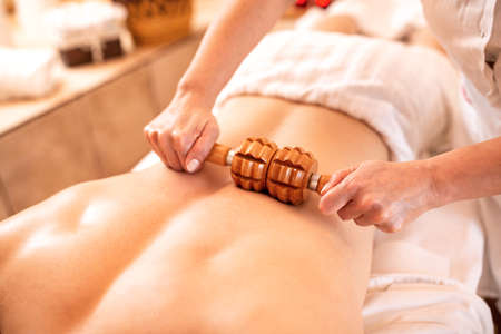 Young sports man having a massage with a wooden roller