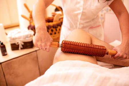 Thigh massage with a stiff wooden roller, circulation stimulation massage Фото со стока