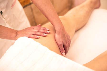 Massaging a thigh of a strong man, relaxation massage concept