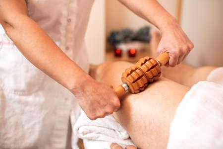 Thigh massage with special wooden instrument, leg massage concept