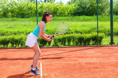 Young woman practicing improvement of serve return in tennis on clay court Stock Photo - 135482345