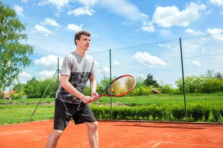 Junger Mann in grau-schwarzem Outfit, der beim Training einen Tennisschläger hält Standard-Bild