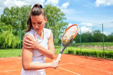 Pretty young girl injured during tennis practice, sport injuries Stock Photo - 135480333