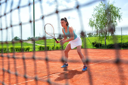 Pretty tennis player observed through the net, concept of tennis Stock Photo - 135480432
