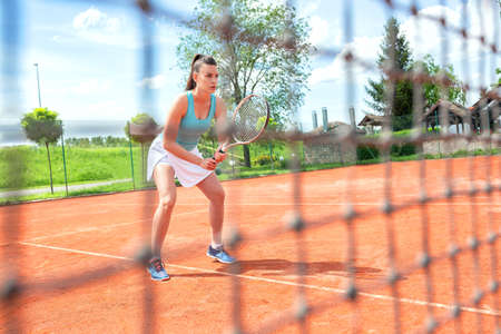 Pretty tennis player observed through the net, concept of tennis