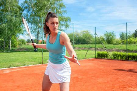 Pretty girl preparing for a forehand stroke in tennis
