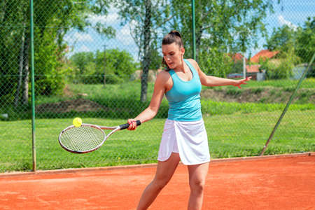 Pretty woman preparing to hit a tennis ball with her racket Stock Photo - 135480157