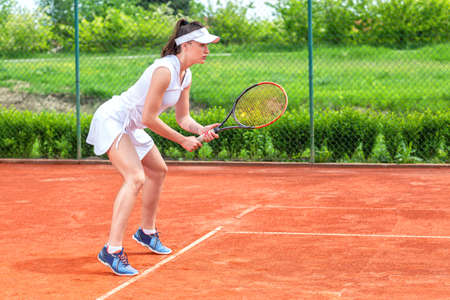 Pretty girl playing tennis outdoors, concept of healthy life in sport