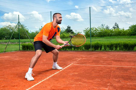 Bearded guy preparing to receive tennis serve, training hard concept