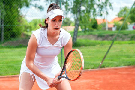Pretty girl dressed in white playing tennis fully focused Stock Photo