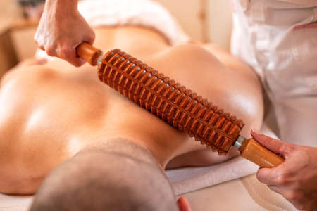 Special massage with a wooden roller tool, blood flow stimulation massage Archivio Fotografico