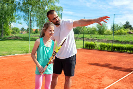Young girl and her tennis coach talking during a practice Stock Photo - 135479913