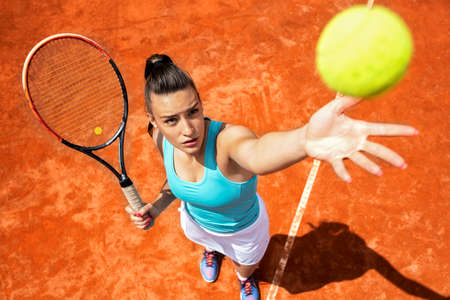 Young woman preparing to make a serve in tennis, serving technique concept Stock Photo - 135480278