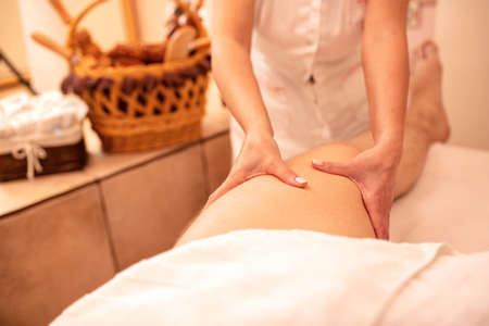 Thigh massage of a young man's leg, massage benefits concept