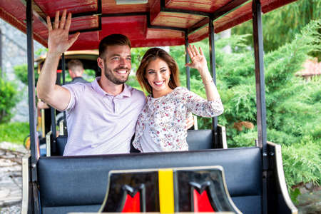 Happy couple sitting in the mini train having a great time Stok Fotoğraf