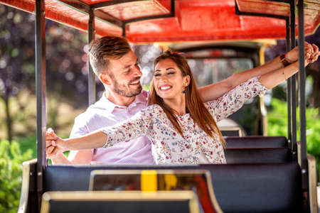 Young couple sharing unforgettable moments during a mini train ride