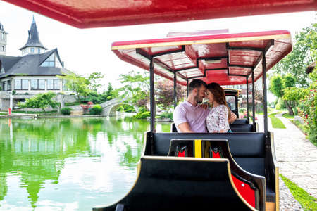 Couple on a romantic mini train ride by the lake