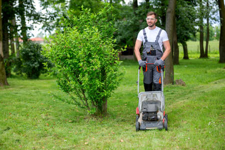Handsome man dressed in lawn mowing outfit with a lawn mower