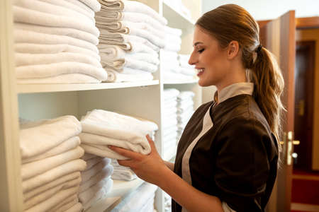 Hotel maid choosing which towels to take to the room