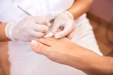Pushing back the cuticles on toes with cuticle pusher Imagens