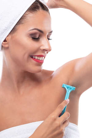 Beautiful young woman shaving her armpit with a green razor