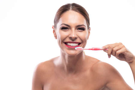 Beautiful woman holding a toothbrush and happily smiling