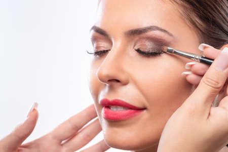 Gros plan d'un joli visage tout en appliquant le maquillage, assorti au bronzage de la peau