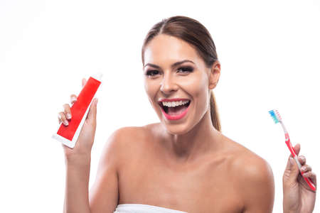 Smiling happy woman holding a tooth paste and a tooth brush, oral hygiene concept