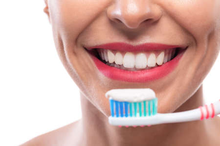 Close up of white teeth and a toothbrush with some toothpaste on it Banque d'images