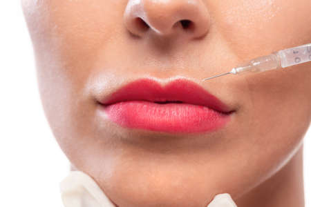 Pretty lady applying skin repairing injection in her face and lips by a cosmetician