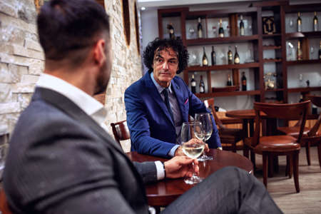 Two bosses having a serious conversation while drinking a glass of wine