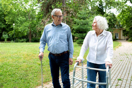 Elder people using walking cane and a walker for a gentle stroll in the park, elder concept