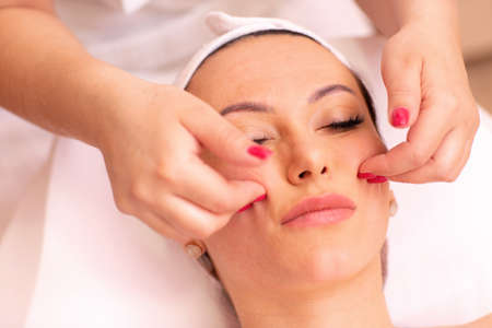 Woman undergoing a facial madero massage in welness center performed only with fingers of a masseuse Stock fotó