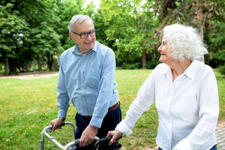 Senior people walking and enjoying a beautiful day in the park using walkers