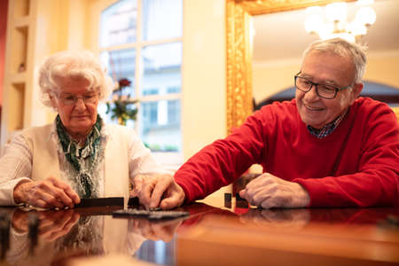Older folks enjoying playing board games in a nursing home Imagens
