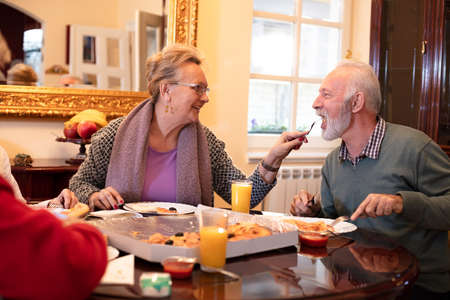 Elderly folks enjoying eating pizza and having a great time