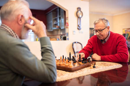 Two senior men outmaneuvering each other while playing chess, senior folks home